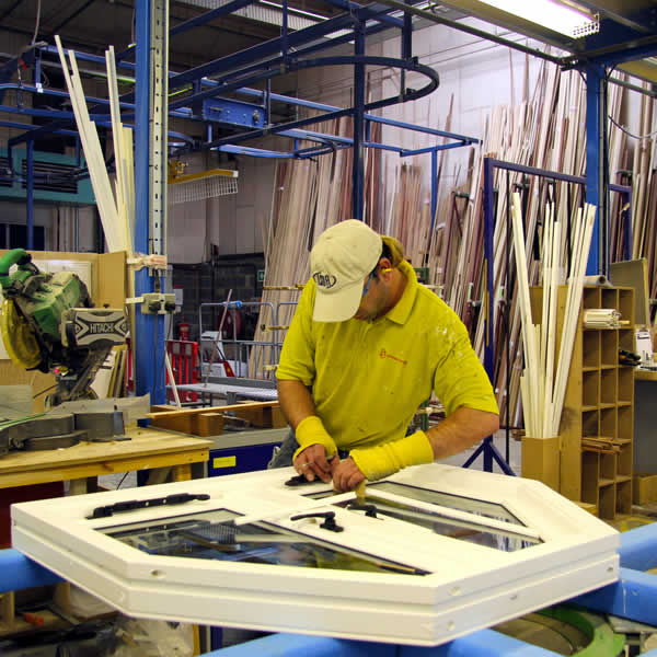 A member of the factory team working on a timber casement window