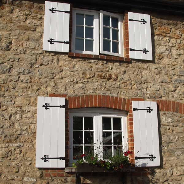 Traditional wooden windows with shutters installed on a cottage